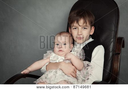 Portrait Of Brother And Sister On Gray Background