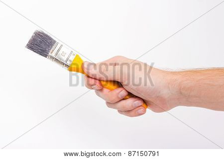 Hand hold yellow handler brush painting on white background.