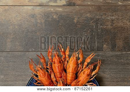 Plate Of Red Crayfishes On Old Wooden Table In Bottom Part
