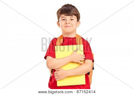 Smiling cute schoolboy with backpack holding books and looking at camera isolated on white background