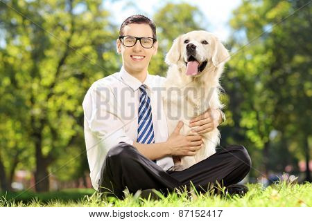Young smiling man sitting on a green grass and hugging his labrador retriever dog in a park