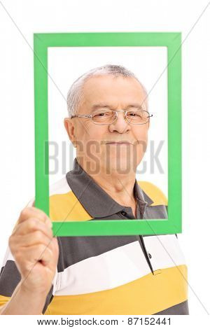 Happy senior posing behind a green picture frame and looking at the camera isolated on white background