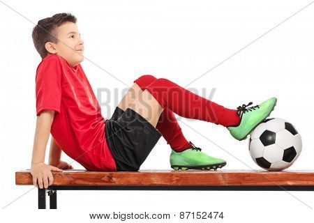 Relaxed young boy in football uniform sitting on a wooden bench and thinking isolated on white