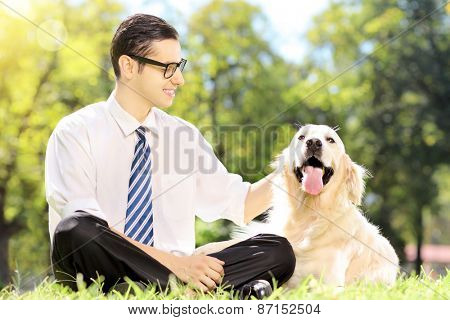 Smiling young businessman with his dog sitting on grass in a park. The dog is golden retriever