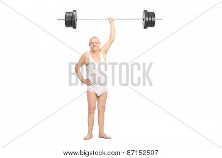 Full length portrait of a semi-dressed senior lifting a heavy barbell with one hand and looking at the camera isolated on white background