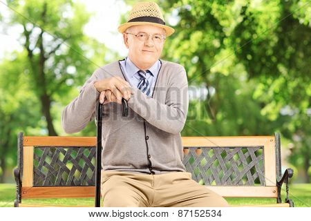Senior man with cane sitting on a wooden bench and looking at camera