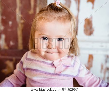 Close-up Portrait Of Funny Blond Little Girl With Big Grey Eyes And Plump Cheeks With Pursed Lips