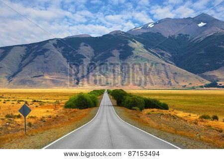 Smooth asphalt road passes between the yellow plains to the distant mountains. Steppes of Patagonia
