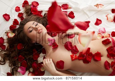 Image of seductive woman showered with rose petals