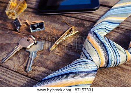 Men accessories: tie, cufflinks, tablet, perfume and keys on the old wood background. Toned image.