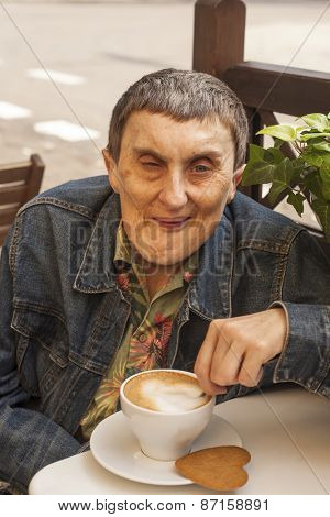 Elderly disabled man with cerebral palsy sitting at outdoor cafe with cup of coffee.