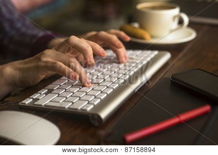 Female office worker typing on the computer keyboard.
