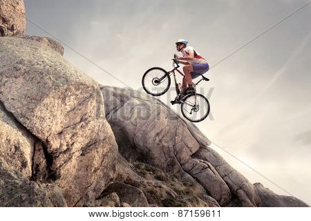 Difficult lifting for cyclist, a man tries to overcome steep slope.