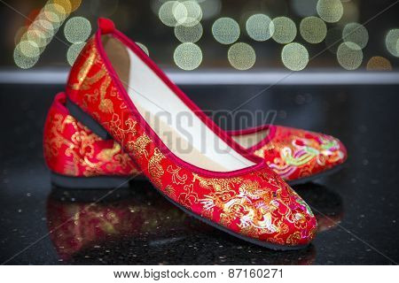 A traditional pair of red wedding shoes.