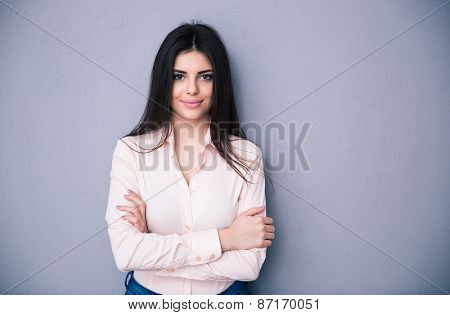 Happy beautiful woman standing with arms folded over gray background. Wearing in pink shirt. Looking at camera
