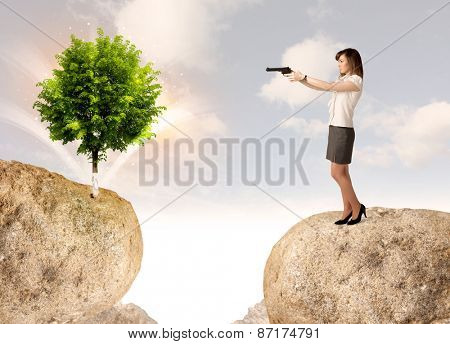 Businesswoman standing on the edge of rock mountain with a tree on the other side
