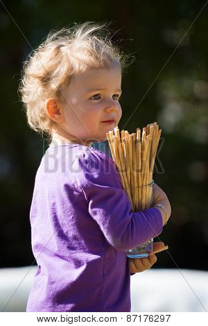cute girl baby with blond hairs holds glass with pretzel salt sticks