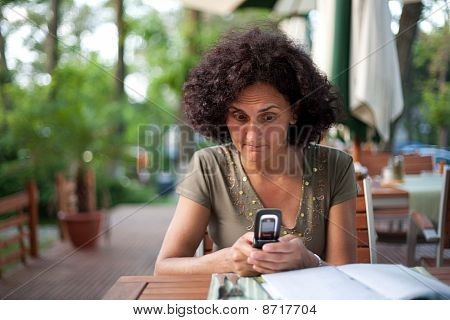 Young Woman Using Cellphone In A Restaurant