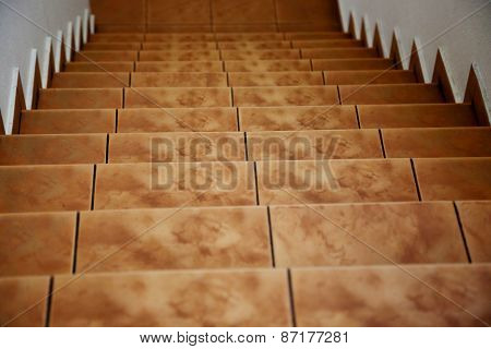 Leading Down Tiled Brown Yellow Stairs