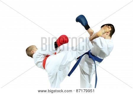 Sportsmens with different belts and overlays on his hands are beating blows kicks