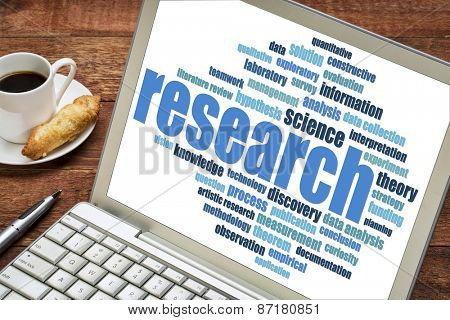 scientific research word cloud on a laptop screen with cup of coffee