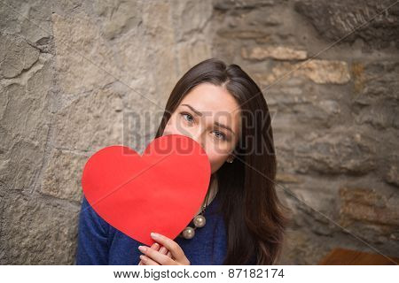 Girl Hiding Behind A Sign In The Form Of Heart