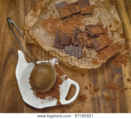 Chocolate pieces and stainer with cocoa powder.