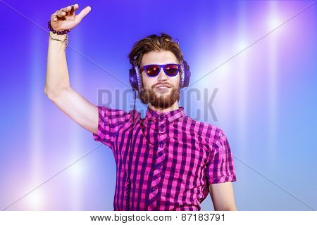 Portrait of a dreamy handsome young man listening to music in headphones. Blue sky background. Leisure, summer, vacation.