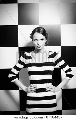 Fashion shot of an elegant model posing in dress in black and white stripes on a background of black and white squares. Beauty, fashion concept.