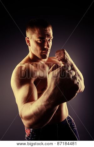 Strong muscular man fighting with fists. Martial arts. Fist fights, boxing. Bodybuilding. Black background.