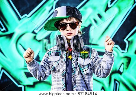 Trendy 7 year old boy on the street. Graffiti background. Modern generation.
