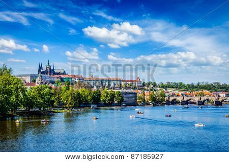 Vltava river and Gradchany (Prague Castle) and St. Vitus Cathedral and Charles bridge with people in paddle boats. Prague, Czech Republic