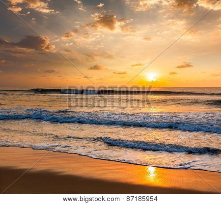 Sunrise with rising sun on morning beach