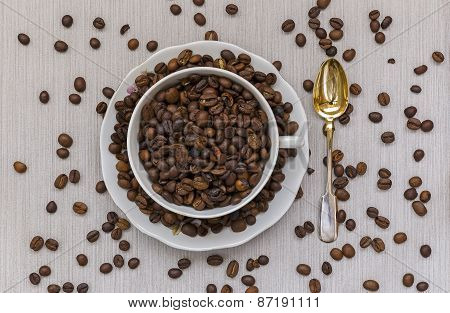 Cup And Saucer Filled With Coffee Beans And Spoon