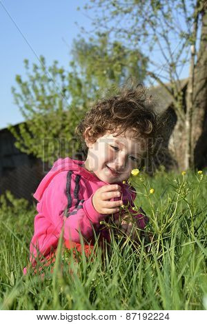 In Summer, The Garden Sits A Little Curly Girl And Sees A Yellow Flower.