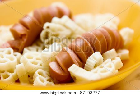 Sausages With Curly Pasta Closeup. Macro