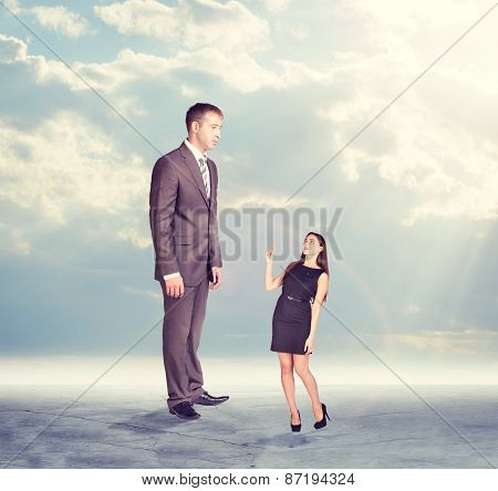 High businessman looking down at little woman in dress