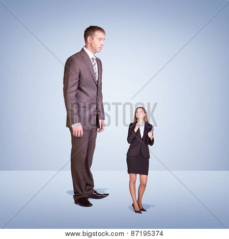 High businessman looking down at little woman with pen and clipboard