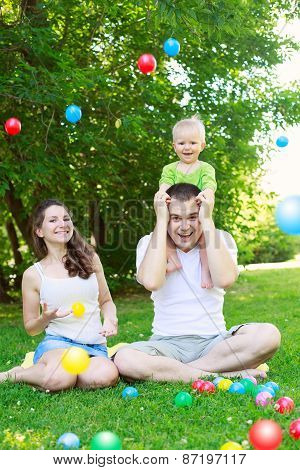 Happy Family  Playing With Colorful Balls In Park