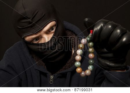 Thief. Man in black mask with a jade necklace. Focus on thief