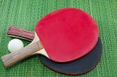 image of ping pong  - Two table tennis rackets and a ping pong ball on green surface - JPG
