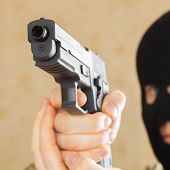 stock photo of gun shot  - Man in mask holding gun and ready to use it  - JPG