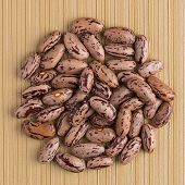 stock photo of pinto bean  - Top view of circle of pinto beans against yellow vinyl background - JPG