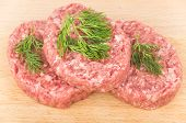 stock photo of ground-beef  - Raw meatballs of ground beef with dill on wooden board - JPG