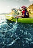 picture of kayak  - Young lady paddling hard the sea kayak - JPG