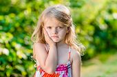 picture of toothache  - Sad little girl with long blond hair suffering from toothache - JPG