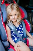 stock photo of seatbelt  - Adorable smiling little girl with long blond hair buckled in car seat looking through the car window - JPG