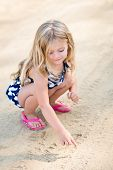 stock photo of squat  - Sweet smiling little girl with long blond hair squatting and drawing in the sand on the beach in summer day - JPG