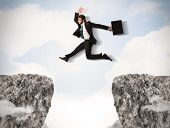 picture of gap  - Funny business man jumping over rocks with gap concept - JPG