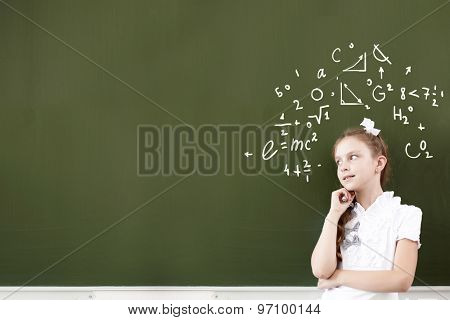 Pretty girl of school age standing at blackboard